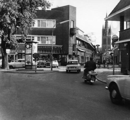 Leesbibliotheek Nooit Gedacht op het kruispunt Herenstraat/Veemarktin Hilversum. Op de achtergrond de St. Vituskerk.