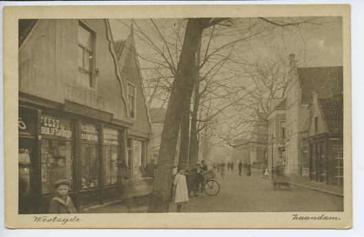 Oude ansichtkaart van hoek Bakkerpad (Klokbaai) in Zaandam. Links leesbibliotheek, tevens gespecailiseerd in verkoop van prentbriefkaarten, feest- en bruiloftsartikelen en verhuur van toneel- en balkostuums