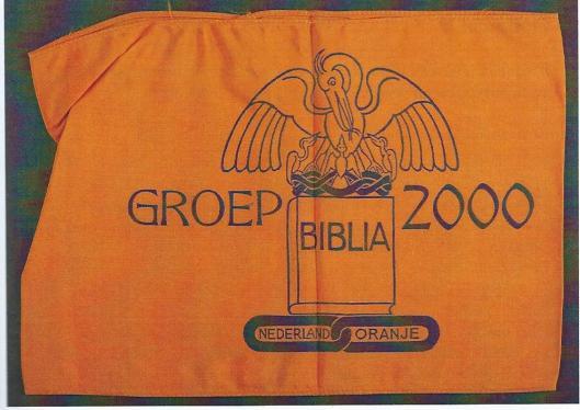 Band met embleem van Groep 2000, ontworpen door Max Nauta. Bovenop de bijbel staat een afbeelding van de Pelikaan-vogel, die zichzelf de borst openrijt om zijn jongen te voeden, een symbool dat is ontleend aan de vrijmetselarij (Uit boek Jacoba van Tongeren, 2015).