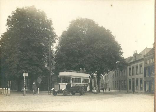 De bus rijdt Haarlem binnen met twee mannen op de imperiaal