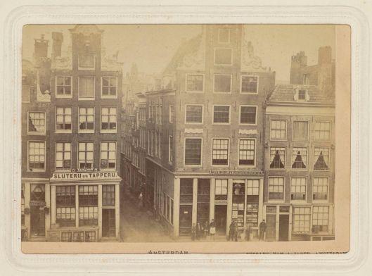 Stilsteeg aan de Nieuwe Zijds Voorburgwal in Amsterdam. Grachtenhuis links: Slijterij en Tapperij; rechts: 'Hollandsche en Fransche Leesbibliotheek' (foto U.B.-Leiden; bijzondere collecties)