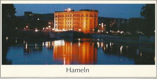 Ansichtkaart van het verlichte gebouw van de stadsbibliotheek in Hameln bij nacht