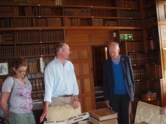 Sir Richard FitzHerbert (midden) toont aan bibliothecaris Hans Krol uit Heemstede een album in zijn bibliotheek (21 juni 2014). Alle 3.500 boeken zijn onlangs gecatalogiseerd met uitzondering van een recente Playboy uitgave.