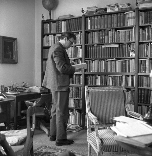 Godfried Bomans een boek raadplegende uit zijn boekenkast in Bloemendaal, 1963 (foto Inez van 't Hoff)