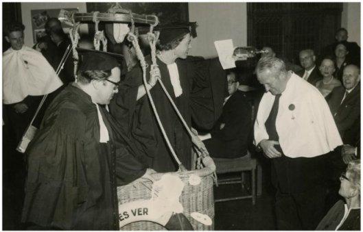 7-1--1956. Een ballonsportbijeenkomst in de Rolzaal. Dr.A.Melchior, gynaecoloog en boekenschrijver, ontvangt de wijndoop door Mini Boesman. Godfried Bomans, bedenker van de ceremonie, kijkt toe (Haagse Beeldbank)
