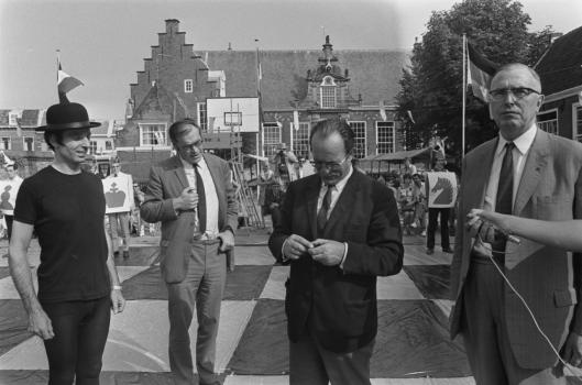 Godfried Bomans en Max Euwe spelen schaak met levende stukken op het Doelenplein, 1970, nu Stadsbibliotheek