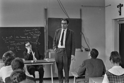 Godfried Bomans bij een bezoek aan der derde klas van het Haarlemse Mendel-college. Links de leraar Nederlands F.X.Koot. Uitgezonden in AVRO-televisieserie 'Uit de school geklapt', 25 februari 1964