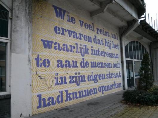 Muurtekst: 'Wie veel reist zal ervaren dat hij het waarlijk interessante aan de mensen ooit in zijn eigen straat had kunnen opmerken' Citaat van Godfried Bomans op muur Onder de Hofbogen te Rotterdam (Dichtbij, 5 november 2014).