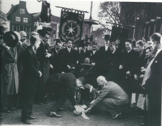 Het Litterarisch Dispuut Gezelschap B.E.E.T.S. uit Leiden hield op 17 november 1955 een bijeenkomst op de Grote markt in Haarlem in aanwezigheid van Godfried Bomans. Vooraan leggen burgemeester Cremers (rechts) en de heer W.E.Haak, voorzitter van het Leidse dispuut een erekrans (NHA)