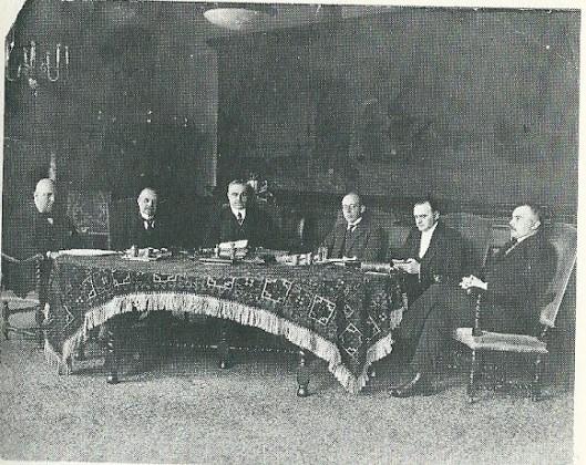 Mr.J.B. bomans 'met witte das' bij een collegevergadering als wethouder van de gemeente Haarlem, tweede van links gezeteld.