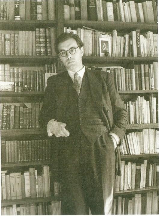 In 1943 is Godfried Bomans vanuit Nijmegen verhuisd naar een huurhuis aan de Zonnelaan 17 in Haarlem. Hier poseert hij voor zijn intussen welgevulde boekenkast
