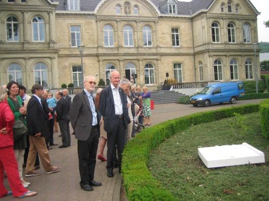 Hans Krol met links van hem schrijver en biograaf Jan Schurgers na de onthulling van een Hanlo-monument op 29 mei 2014 in Valkenburg. Op de achtergrond het gebouw Geerlingshof