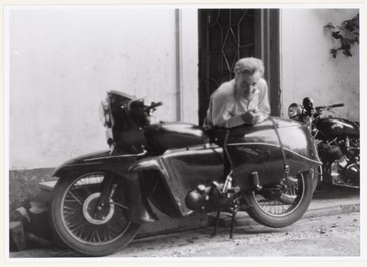 Jan Hanlo poserend met twee motoren voor de ingang van zijn huisje bij Geerlingshof