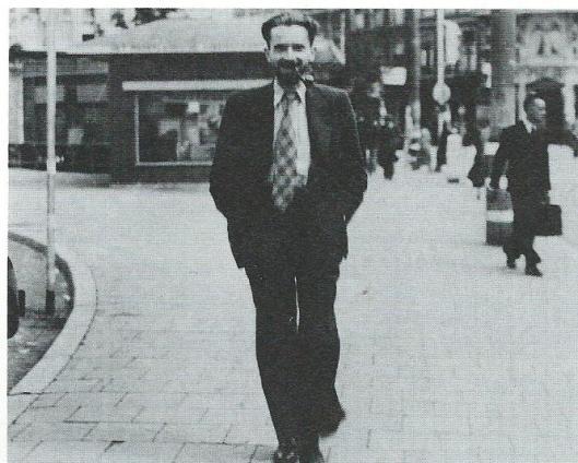 Jan Hanlo met pijp wandelend in Amsterdam