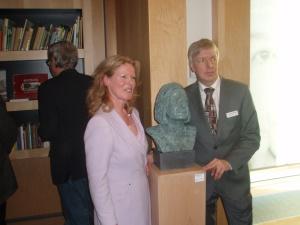Rechts directeur Hans van Velzen naast het borstbeeld en voor kast met Hella Haasse-boeken