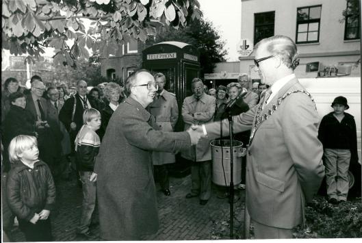 17-101981 droeg mayor Norman Parker van Royal Leamington Spa een Britse telefooncel over aan Heemstede middels een handdruk met burgemeester Van den Bosch. In het idden staat Cees Sprangers en links van hem Peter Barton, toenmalig voorzitter van de Leamington International Friendschip Society