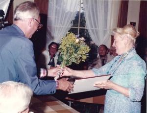 Voorzitter Gerard Schuitemaker reikt bloemen een een oorkonde uit aan Coby Roemersma in 1982 bij gelegenheid van haar erelidmaatschap van de VOHB/HVHB. Oud-voorzitter, rechts achter gezeten, kijkt toe.