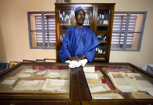 Een conservator bij de oude Islamitische handschriften in de Ahmed Baba bibliotheek in Timboektoe (foto Ben Curtis/AP)