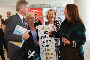 Begroeting van 10 miljoenste bezoeker OBA (rechts) met links directeur Hans van Velsen en in het midden minister Jet Bussemaker