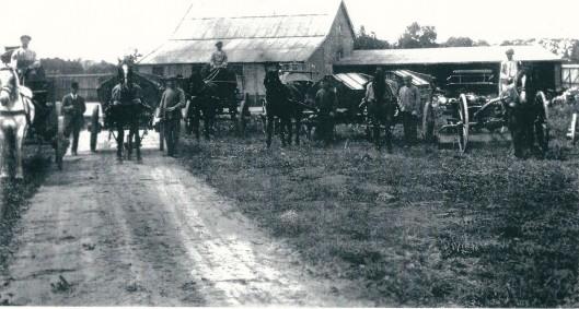 Foto uit 1914 toen de reiniging werd gepacht door Romke de Jong. Op deze afbeelding poseert hij met bolhoed, geflankeerd door 6 personeelsleden met hun paard en wagen. Op de achtergrond de werkplaatsen/schuren aan de Cruquiusweg