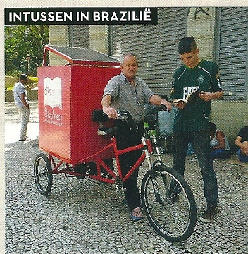 Een zwerfbieb/bibliofiets met Robson Mendonca (62) in Brazilië (Katy Sheriff) In Sao paula ruijden nu 13 van dergelijke biebfietsen rond die afgelopen jaar 1.380 boeken uitleenden.