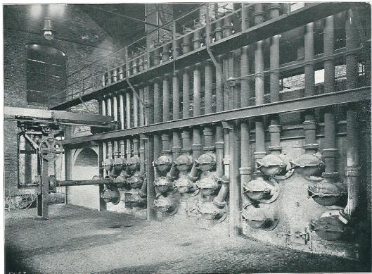 Foto van de stokerij in 1909. Rechts het ovenblok waarin drie ingebouwde ovens en een lege kluis. Duidelijk zichtbaar zijn de retortenmonden met de z.g. klimpijpen, dienende tot afvoer van het gas uit de met steenkolen geladen retorten. Voor één der retorten bevindt zich de laadmachine.