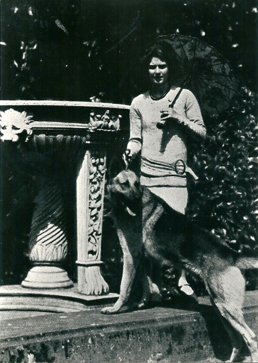 Ursula von Pannwitz met haar Duitse herder bij een prieel op de Hartekamp