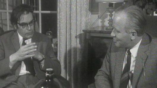 Godfried Bomans en Michel van der Plas in overleg met een fles op tafel