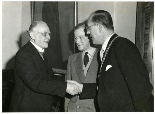 Burgemeester mr.F.M.A.Schlichting feliciteert professor Gerritsen met de uitreiking van de Constantijn Huygensprijs, 12-10-1950. In het midden Michel van der Plas.