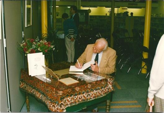 Michel van der Plas tekent het gastenboek bij de opening in 1978 van een tentoonstelling over Godfried Bomans in de openbare bibliotheek van Waddinxveen