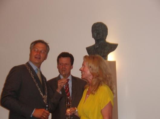 Burgemeester mr. Bernst Schneiders, mr. Frank Mulder en beeldhouwster Ellen Wolff toasten op het resultaat.