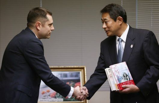 Israel Embassy representative Peleg Lewi, left, shakes hands with Japan's Sugimani Ward mayor Ryo Tanaka Thursday. The Embassy donated 300 Anne Frank Books after copiesin Tokyo's libraries were vandalized (Shizo Kambayashi/AP)