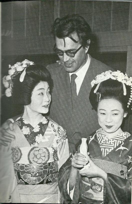 Godfried Bomans wordt in het land van de rijzende zon verwelkomd door twee geisha's bij aankomst op het vliegveld van Tokio als eregast van de KLM na de inaugurele vlucht over de Noordpool naar Japan.
