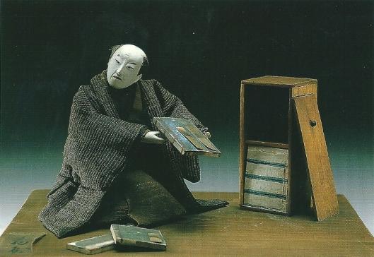 De boekverkoper, uit een serie Japanse ambachtpoppen uit eerste helft 19e eeuw (collectie Rijksmuseum voor Volkenkunde Leiden)