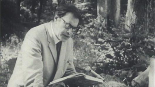 Foto van Godfried Bomans in de natuur voorlezend uit zijn boek Erik