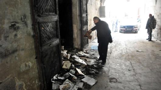 Een foto met een restant van verbrande boeken in Tripoli. Een soldaat houdt op afstand toezicht.