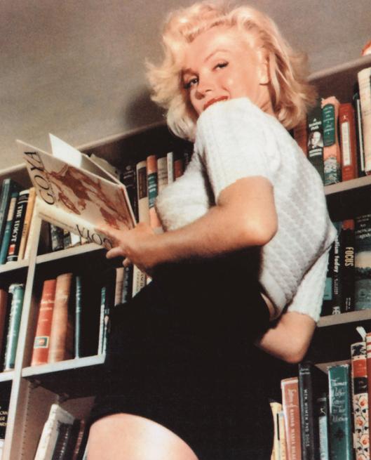 Marilyn Monroe bij haar privé-boekenkast. Na haar overlijden is haar boekenbezit gecatalogiseerd en op de site LibraryThing geplaatst