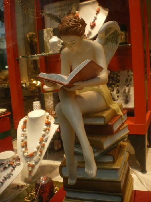 Beeld van vrouw met boek gezeten op boeken (foto Frank Divendal)