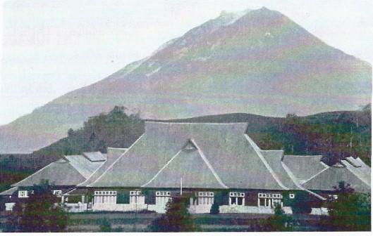 Het hoofdgebouw van de Planters School Vereniging (PSV) in Brastagi. Links enn rechts de twee afdelingen, elk met vier slaapzalen. Op de achtergrond de berg Sinaboeng