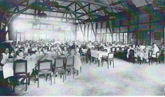 Overzicht van de eetzaal in Brastagi. Aan het hoofd van de voorste tafels: links juffrouw Gräber en helemaal rechts (directeur) Marsman. Foto uit 1935.