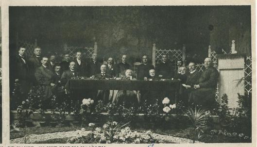Op het podium het bestuur van de Hanze in 1917. In het midden achter de grote tafel zit bisschop mgr. Callier. Staande vijfde van links is commissaris mr.J.B.Bomans