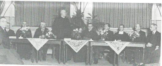 Een vergadering oude stijl in het Verenigingsgebouw. Staand pastoor H.IJzermans en rechts van hem plebaan Westerwoudt. Helemaal rechts zit kerkmeester Jac.H. Kramer (voor wiens huis 'Mariahof' aan de Kerklaan op 13 november 1944 een V-1 neerstortte).