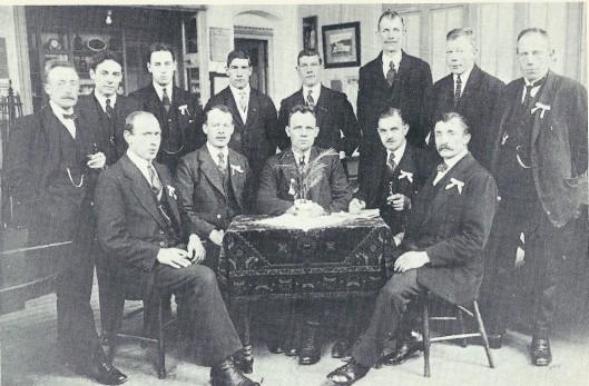 Leden van de pluimveevereniging ter vergadering in de gelagkamer van het Vereenigingsgebouw. Links aan de tafel zit de heer Neeskens. Staande van links af: De Groot, Swinkels, De Wilde, Leuven en als laatste twee telgen uit het tuinliedengeslacht C. en A. van Iperen.