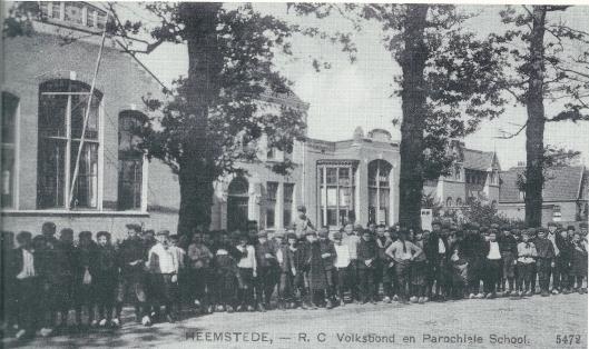 Een oude ansichtkaart van het r.k. Vereenigingsgebouw en rechts daarvan de Sint Jozef-jongensschool, Alle leerlingen dragen een pet en hebben klompen aan.