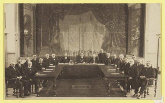De gemeenteraad van Haarlemmermeer in 1919. Achterste rij v.l.n.r.: J.A.Overmeer, P.Ouwerkerk, L.van Andel, W.van Sloten. Voorste rij: C.v.d.Laan, A.P.Stokman, J.Suidgeest, J.Kooy. Achterste tafel: P.Borst (wethouder), mr.A.Slob (burgemeester), N.J.Rinkel (secretaris). Staand: D.Langereis (portier), G.A.Knaap (wethouder),. Rechter tafel voorste rij: C.J.van Mansum, H.van Schooten, K. Kistemaker, A.Rombout. Achterste ij: Chr. van den Heuvel, A.Roodenburg en Joh.Verkuijl Pzn.