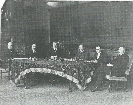 Een foto van het college van Burgemeester en wethouders Haarlem. Mr.J.B.Bomans , met wiitte das, tweede van links