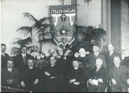 Het Genootschap van de Stille Omgang op een foto uit 1932. Op de voorste rij v.l.n.r,: W.Grioenland, kapelaan J.M.Brinkman, pastoor J.van der Tuyn, kapelaan Tesselaar, H.Kriefer en L.van der Vosse. Staande: Q.van der Peijl, J.Steinhof, Jan Wiegman en P.de Wildt. Jet vaandel was ontworopen door Jan Wiegman.