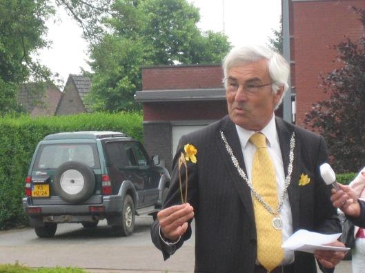 Burgemeester Eurlings plaatst een narcis op de gedenksteen en plant een narcis in de omliggende tuingrond