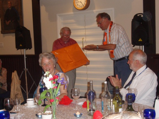 Voorzitter Leon Christophe (rechts) biedt in oranje verpakking een cadeau aan aan voorzitter John Mather van de Leamington International Friendship Society
