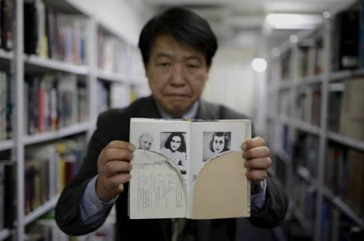 Bibliothecaris Kotaro Fujimaki toont een toegetakeld dagboek van Anne Frank